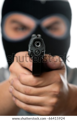 An angry looking man wearing a ski mask pointing a black handgun at the viewer. Works great for crime or home security concepts. - stock photo