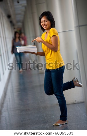 An angry young college student points at her textbooks with a disgusted expression.  20s female Asian Thai model of Chinese descent. - stock photo