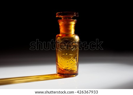"""An antique and vintage glass bottle for pharmaceutical use of """"Teinture d'iode"""" (means Tincture of iodine), that is an antiseptic medicine, isolated on a dark background. - stock photo"""
