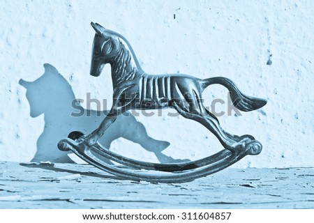 An antique brass rocking horse with its shadow, in blue tones - stock photo