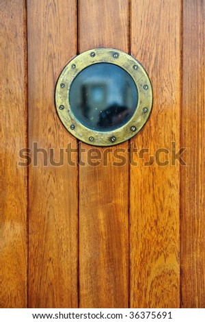 an antique doorway with porthole from a ship - stock photo