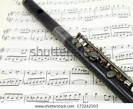 An antique flute on a sheet of old music. - stock photo