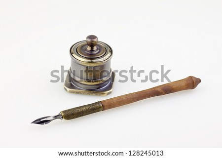 An antique metallic inkwell and old pen isolated background - stock photo