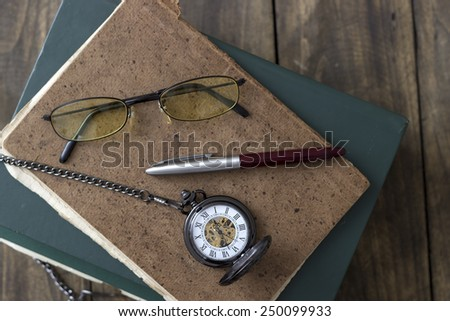 An antique pocket watch, glasses and books, from above - stock photo