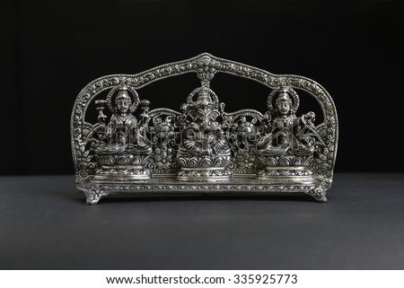 An antique statue of Lord Ganesha, Goddess Laxmi and Saraswati.   - stock photo