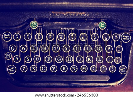 an antique typewriter on a wooden table toned with a retro vintage instagram filter effect app or action  - stock photo