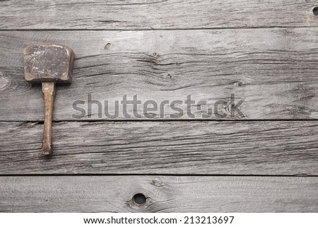 An antique wooden mallet on a background of grey barn board with lots of room for your copy. - stock photo