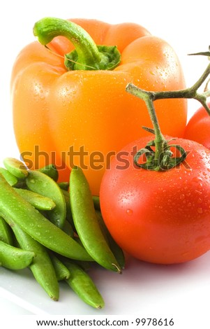 An appetizing yellow bell pepper,red tomato and green peas sit on a white surface. - stock photo