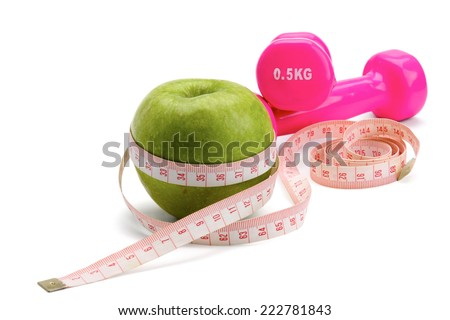 An apple, a measuring tape and dumbbell. - stock photo