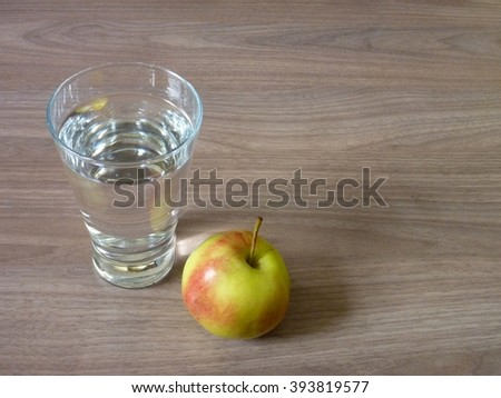 an apple and a glass of pure water - stock photo