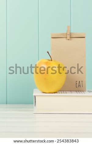 An apple and a paper bag with lunch on a book. A white wooden table with a robin egg blue wainscot. Vintage Style. - stock photo
