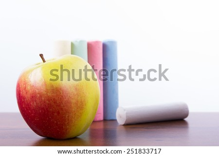 An apple and chalk. Back to school background. - stock photo