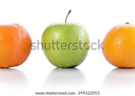 An apple between two oranges, isolated on white background - stock photo