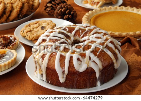 An apple bundt cake with caramel glaze and frosting and other holiday treats - stock photo