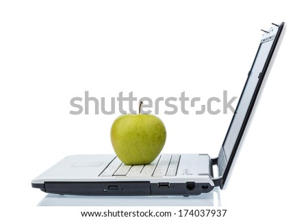 an apple is on the keyboard of a computer. symbolic photo for vitamin-rich and healthy snack. - stock photo