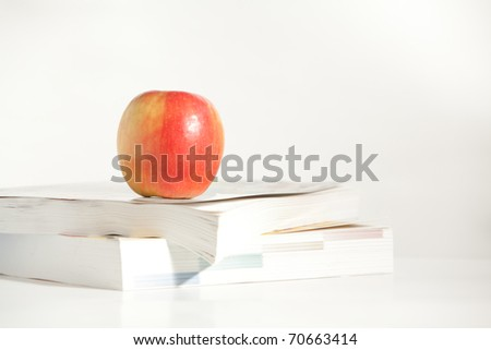 An Apple on a Stock of Books in the studio - stock photo