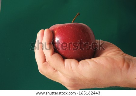 An Apple on the Hand over a Colored Background - stock photo