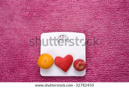 An apple, orange and heart placed on scales, shot landscape. - stock photo