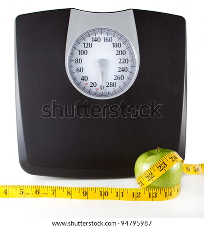 An apple with a measuring tape around it with a scale in the background, white background. Room for copy-space on the scale. - stock photo