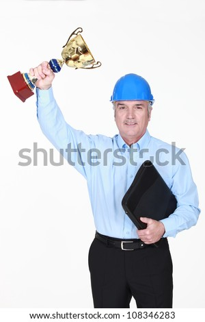 An architect holding  a trophy cup. - stock photo