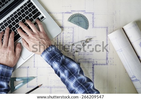 an architect working with blueprints and a laptop computer - stock photo