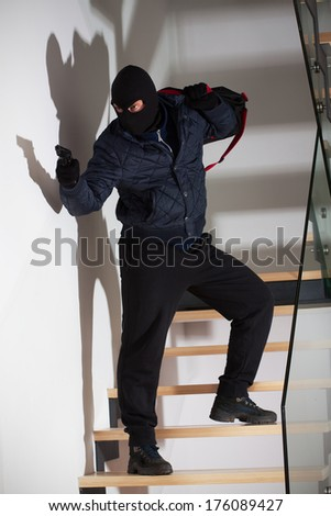 An armed masked robber waiting on the stairs to attack - stock photo