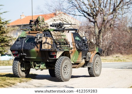 An armoured vehicle of the foreign Legion on patrol of the area. Soldier of french foreign legion in observation.  - stock photo