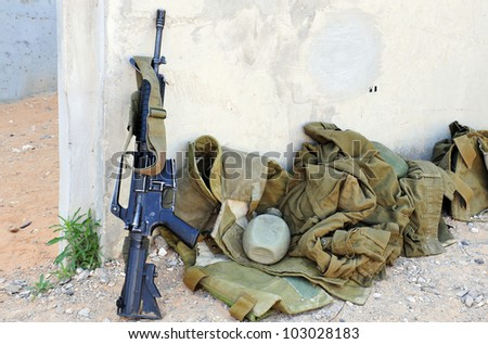 An army weapon and uniform in a war zone. Concept photo of war zone, war, armed conflict, weapon and war crimes, treaty, agreement, ceasefire or truce. - stock photo