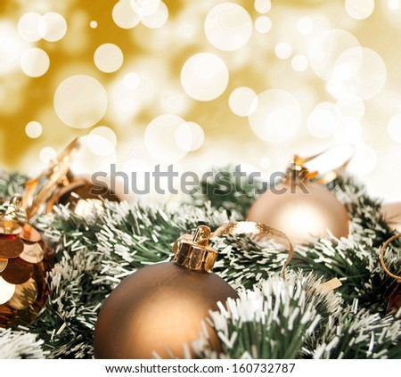 An arrangement of golden Christmas baubles against a festive bokeh of twinkling gold lights with copyspace - stock photo