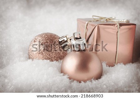 An arrangement of pale peach pink Christmas decorations sinking into soft, white artificial snow.  Includes glitter and matte  baubles and gift box. Pale hues with a vintage vignette. - stock photo
