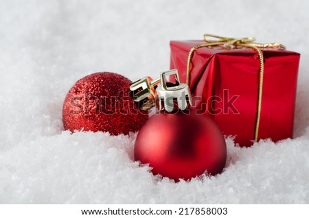 An arrangement of red Christmas decorations sinking into soft, white artificial snow.  Includes glitter and matte  baubles and gift box. - stock photo
