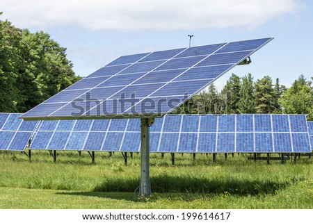 An array of solar panels on a farm in Vermont. - stock photo