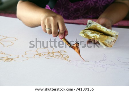 An artist carefully trace the floral motif on a traditional batik fabric using melted wax - stock photo