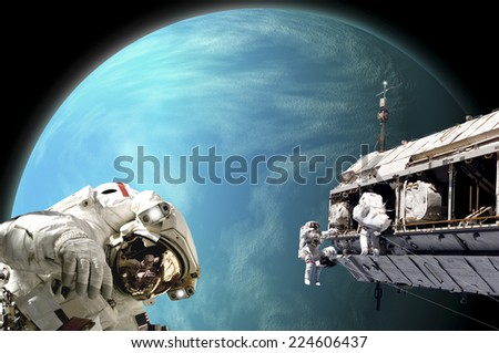 An artist's depiction of  a team of astronauts performing work on a space station while orbiting a large, alien planet. Some elements courtesy of NASA. - stock photo