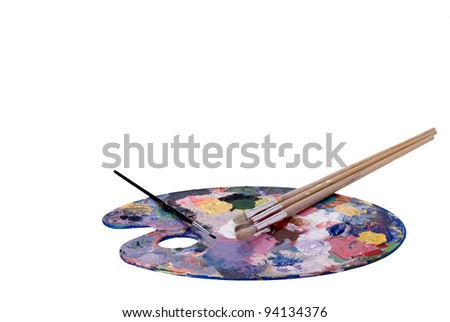 An artist's palette and paint brushes - stock photo