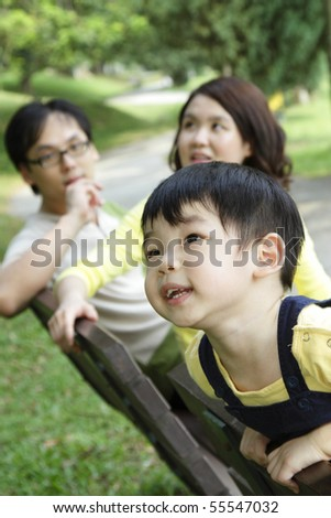 An Asian child at a bench with his parents in the background - stock photo