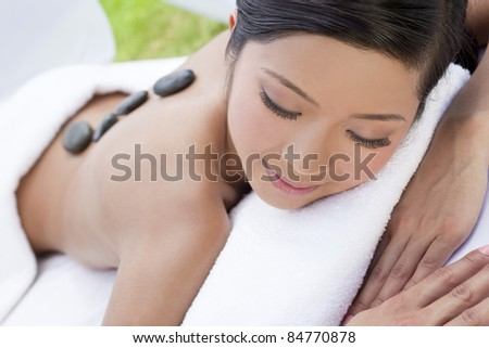 An Asian Chinese woman relaxing outside at a health spa while having a hot stone treatment or massage - stock photo