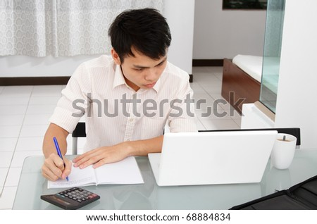 An Asian college student doing homework at home - stock photo