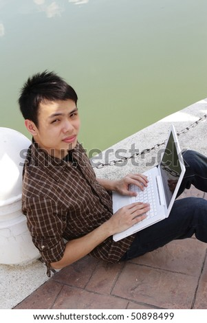 An Asian college student working with his laptop by a lake - stock photo