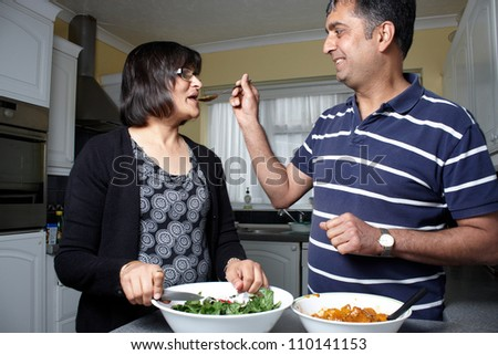 An Asian couple tasting food in the kitchen - stock photo