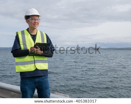 An asian engineer holding a clip board and standing in front of semi submersible oil rig - stock photo