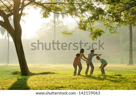 an asian family having fun playing in the park early morning  - stock photo