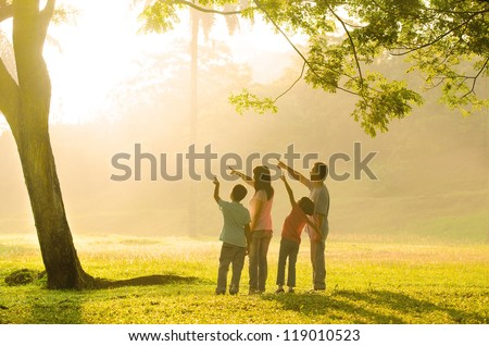 an asian family pointing to somewhere during a beautiful sunrise, backlight - stock photo