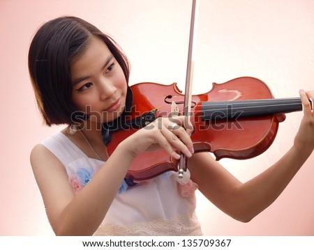 An Asian girl playing violin - stock photo