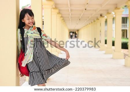 An asian girl portrait, standing lean the pillar, smiling face - stock photo