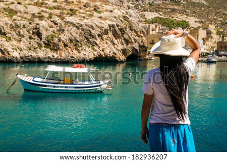 An asian lady enjoys the view over the waters of Xlendi Bay at Gozo Island, part of the maltese archipel - stock photo
