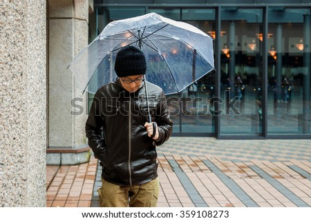 An Asian Man in a Brown Jacket is Strolling in a Street While It's Raining With a Clear Umbrella - stock photo