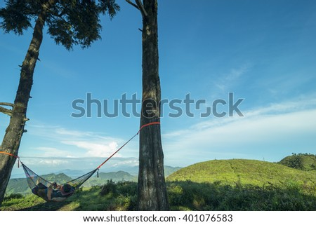 An Asian man playing with his mobile phone while relaxing in a hammock. - stock photo