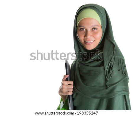 An Asian Muslim Malay woman with green hijab and a laptop over white background - stock photo