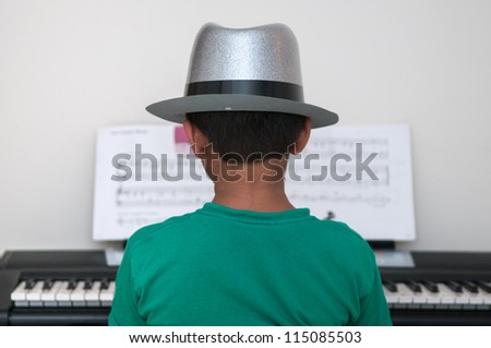 An asian toddler performing at the piano - stock photo